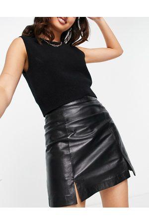 Muubaa Minifalda negra con abertura delantera de cuero de